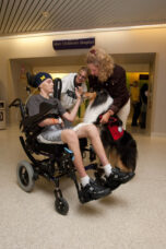 A volunteer and her therapy dog visit with a patient and his aunt at the U-M Health System.