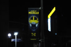 A Michigan football banner is illuminated by street lights with the stadium's giant scoreboard in the background.