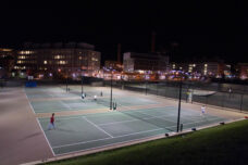 Students play a late night game of tennis at Palmer Field courts outside of the Mosher-Jordan Residence Hall.