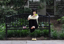 A music student visiting from Korea reads notes while relaxing on a bench at the U-M Law Quad.