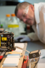 A researcher monitors a robotic instrument handling liquid pharmaceuticals at the Center for Chemical Genomics.