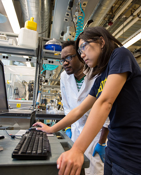 Faculty and students collaborate at an electrochemical workstation in the Phoenix Memorial Lab